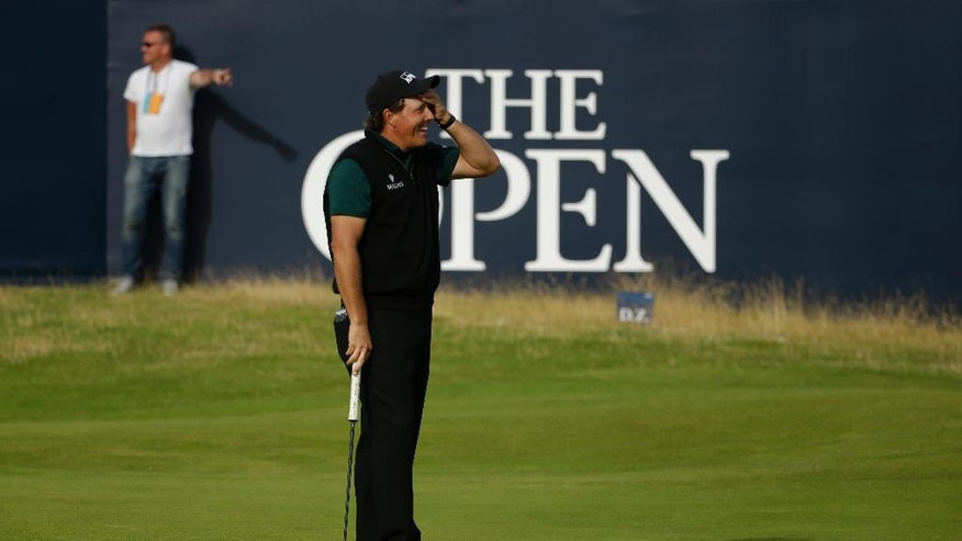 Phil Mickelson of the United States reacts as  he narrowly misses a birdie putt on the 18th green during the first round of the British Open Golf Championships at the Royal Troon Golf Club in Troon, Scotland, Thursday, July 14, 2016. (AP Photo/Matt Dunham)