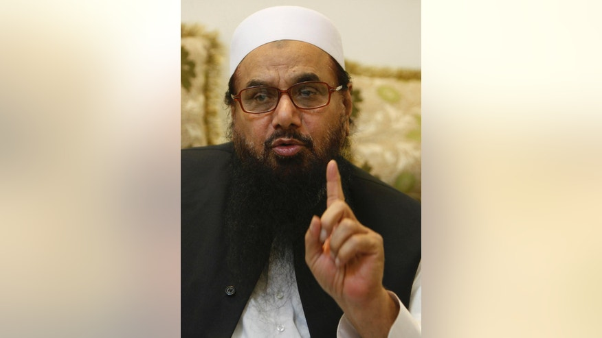 In this photo taken on Wednesday, July 13, 2016, Hafiz Saeed, leader of Pakistani religious group talks to The Associated Press in Lahore, Pakistan. Roaming freely in Pakistan, despite a $10 million bounty on his head, one of India's most wanted men, Saeed warns of demonstrations countrywide to force Pakistan to sever all ties with the United States if it cannot convince Washington to intervene in the decades old Kashmir dispute.(AP Photo/K.M. Chaudary)