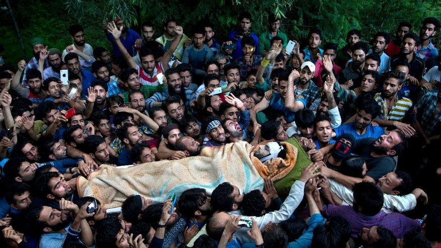 FILE- In this July 9, 2016 file photo, Kashmiri villagers carry the body of Burhan Wani, chief of operations of Indian Kashmir's largest rebel group Hizbul Mujahideen, during his funeral procession in Tral, some 38 Kilometers (24 miles) south of Srinagar, Indian controlled Kashmir. Roaming freely in Pakistan, despite a $10 million bounty on his head, one of India's most wanted men, Hafiz Saeed warns of demonstrations countrywide to force Pakistan to sever all ties with the United States if it cannot convince Washington to intervene in the decades old Kashmir dispute. (AP Photo/Dar Yasin, File)