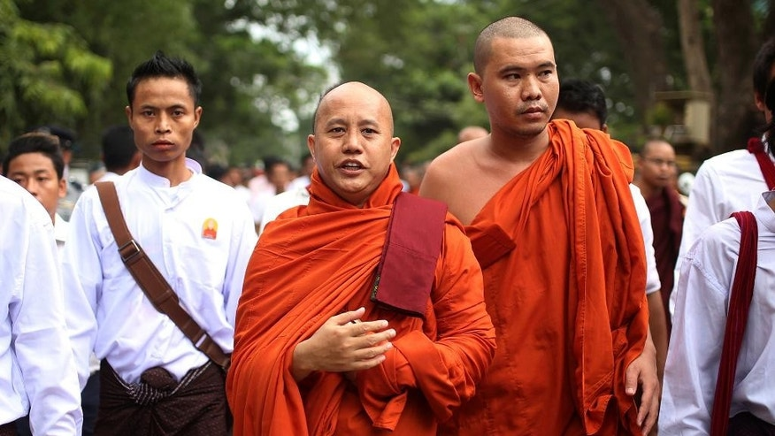 "FILE - In this Sept. 21, 2015 file photo, nationalist Buddhist monk Wirathu, center, marches in Mandalay, the second largest city in Myanmar. Myanmar's government has denounced an influential Buddhist nationalist group, led by Wirathu, after failing to speaking against it strongly while others were accusing it of using hate speech and inspiring violence against Muslims. The Ma Ba Tha organization's charismatic leader Wirathu responded Wednesday, July 13, 2016 by calling the country's de facto leader, Aung San Suu Kyi, a ""woman dictator."" (AP Photo/Hkun Lat, File)"