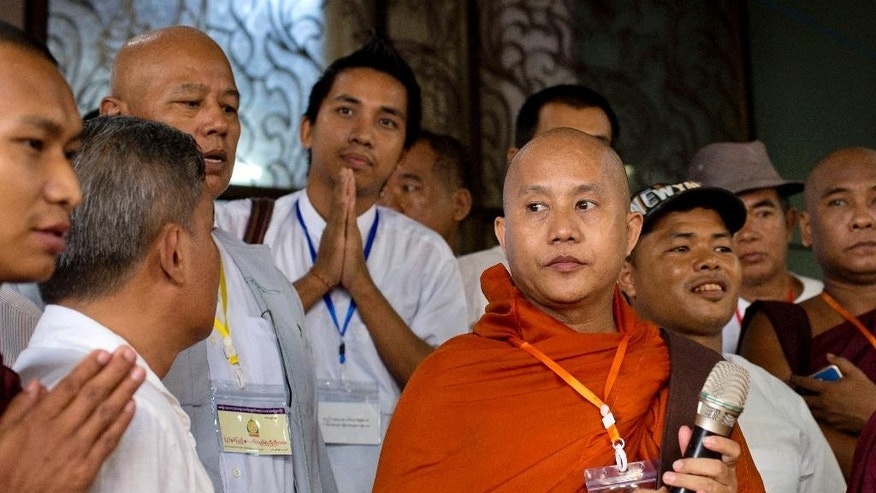FILE - In this June 4, 2016 file photo nationalist Buddhist monk Wirathu, holding a microphone, prepares to address devotees during a ceremony of Organization for the Protection of Race and Religion, known as its' Burmese abbreviation Ma Ba Tha at a Buddhist monastery in the suburbs of Yangon, Myanmar. Myanmar's government has denounced the influential Buddhist nationalist group, led by Wirathu, after failing to speaking against it strongly while others were accusing it of using hate speech and inspiring violence against Muslims. (AP Photo/Gemunu Amarasinghe, File)