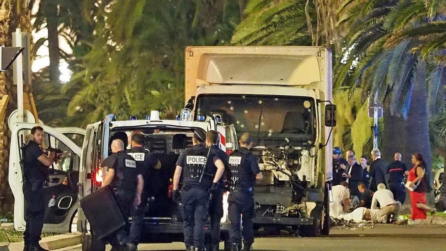 Police stand by as medical personnel attend a person on the ground, right, in the early hours of Friday, July 14, 2016, on the Promenade des Anglais in Nice, southern France, next to the lorry that had been driven into crowds of revelers late Thursday. France has been stunned again as a large white truck killed many people after it mowed through a crowd of revelers gathered for a Bastille Day fireworks display late Thursday evening, in the Riviera city of Nice. (AP Photo)