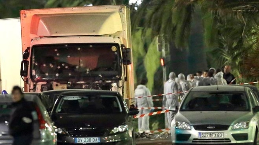 Forensic officers stand near a truck that plowed through a crowd in Nice, southern France, Friday, July 15, 2016.