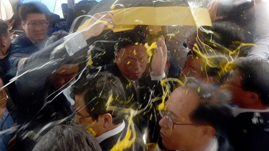 South Korean Prime Minister Hwang Kyo-ahn, bottom center, is shielded by his bodyguards from eggs thrown by residents at Seongju County Office, South Korea, Friday, July 15, 2016. Angry residents in a rural South Korean town have thrown raw eggs and water bottles at the prime minister to protest a plan to deploy a U.S. missile defense system in their neighborhood. (Kang Jong-min/Newsis via AP)
