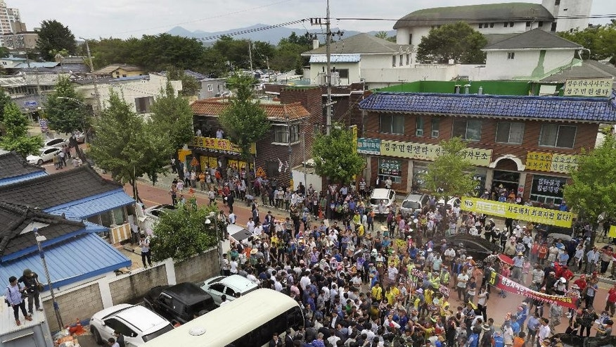 Residents block a bus carrying South Korean Prime Minister Hwang Kyo-ahn in Seongju, South Korea, Friday, July 15, 2016. Angry residents in a rural South Korean town have thrown raw eggs and water bottles at the prime minister to protest a plan to deploy a U.S. missile defense system in their neighborhood. (Shon Dae-sung/Yonhap via AP)