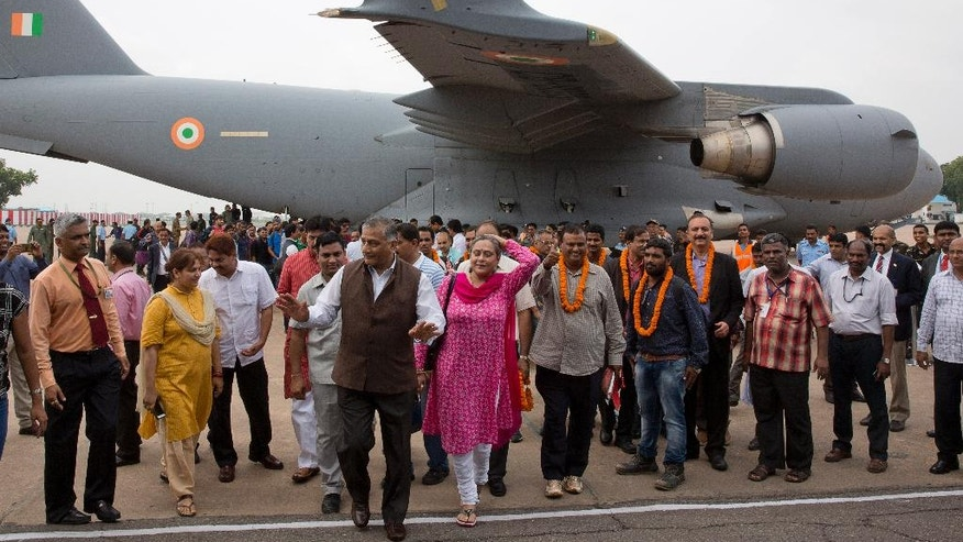Indians evacuated from South Sudan arrive at Palam airport with Indian junior foreign minister V.K. Singh, in brown waist jacket, in New Delhi, India, Friday, July 15, 2016. At least 156 Indians were evacuated from the violence-hit South Sudan, with 71 arriving by a special Indian Air Force flight to New Delhi. The evacuation was part of Operation Sankat Mochan launched by the Indian government. (AP Photo/Manish Swarup)