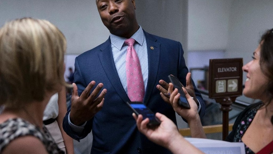 FILE - In this June 21, 2016, file photo, Sen. Tim Scott, R-S.C., talks with reporters on Capitol Hill in Washington. Scott candidly described being stopped by police and Capitol Hill cops because of the color of his skin. It's an experience all too familiar to many of his African-American colleagues in Congress. A day after Scott's personal recounting on the Senate floor, several lawmakers said July 14, that they have had similar experiences. (AP Photo/Alex Brandon, File)
