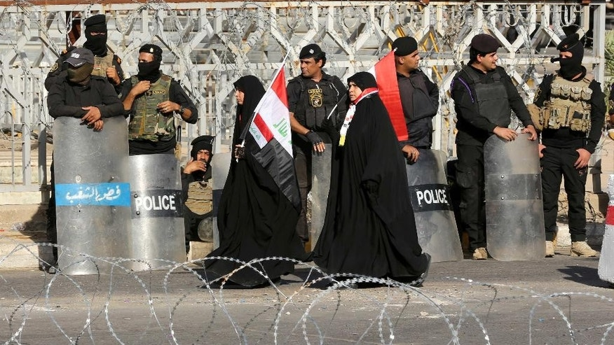 Iraqi security forces close a bridge leading to the heavily guarded Green Zone during a demonstrating supporters of Shiite cleric Muqtada al-Sadr at Tahrir Square in Baghdad, Iraq, Friday, July 15, 2016. Tens of thousands of supporters of a powerful Iraqi Shiite cleric have rallied in central Baghdad to press demands for reform and an end to alleged corruption in the government. (AP Photo/Hadi Mizban)