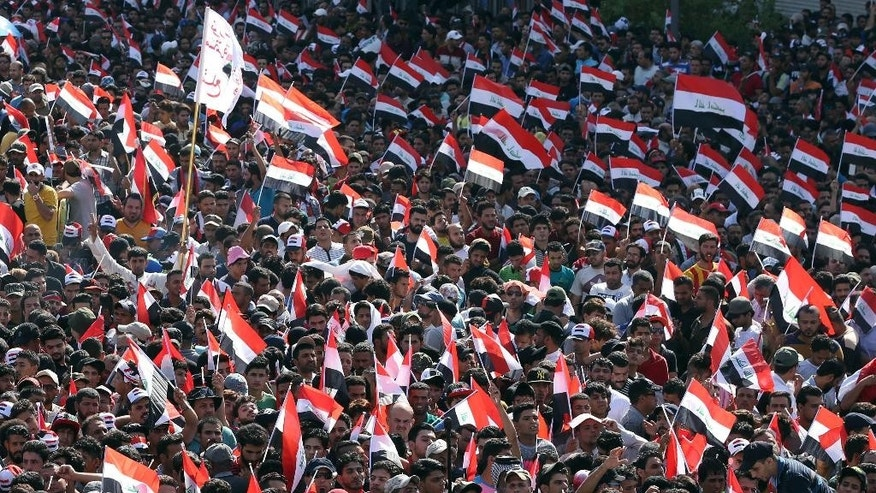 Supporters of Shiite cleric Muqtada al-Sadr demonstrate at Tahrir Square to press demands for reform and an end to alleged corruption in the government as they wave Iraqi flags in Baghdad, Iraq, Friday, July 15, 2016. (AP Photo/Hadi Mizban)