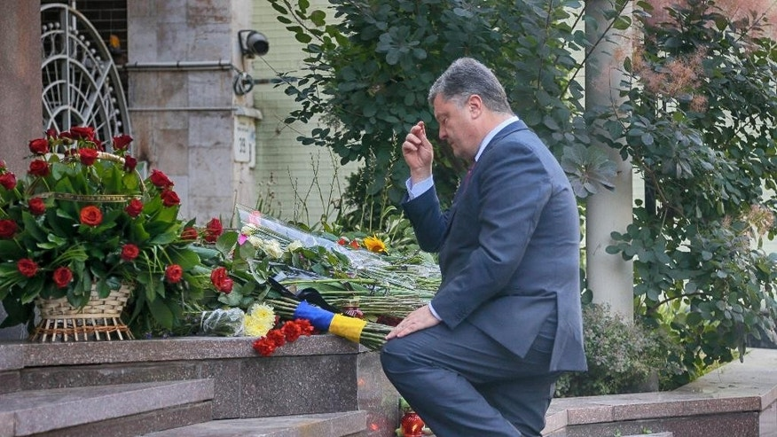 Ukrainian President, Petro Poroshenko, makes the sign of the cross after laying flowers at the steps of the French Embassy in Kiev, Ukraine, Friday, July 15, 2016, to pay tribute to victims of an attack in the French city of Nice. A large truck mowed through revelers gathered for Bastille Day fireworks in Nice, killing more than 80 people and sending people fleeing into the sea as it bore down for more than a mile along the Riviera city's famed waterfront promenade. (AP Photo/Efrem Lukatsky)