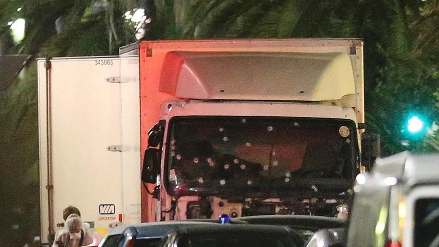 A policeman stands, watching the truck used for the attack near the scene of an attack after a truck drove onto the sidewalk late Thursday, and plowed through a crowd of revelers who gathered to watch the fireworks in the French resort city of Nice, southern France, Friday, July 15, 2016.  (AP Photo/Luca Bruno)