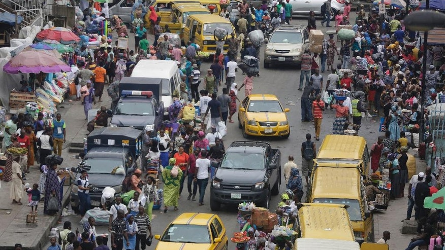 In this photo taken Monday June 20, 2016, pedestrians shop at a market in Lagos, Nigeria. Officials in Nigeria's biggest city are closing down dozens of churches, mosques and nightclubs in a bid to reduce noise in Lagos, the seaside commercial center where honking horns and thrumming generators compete with lusty hymn-singing and loudspeakers calling people to prayer. (AP Photo/Sunday Alamba)