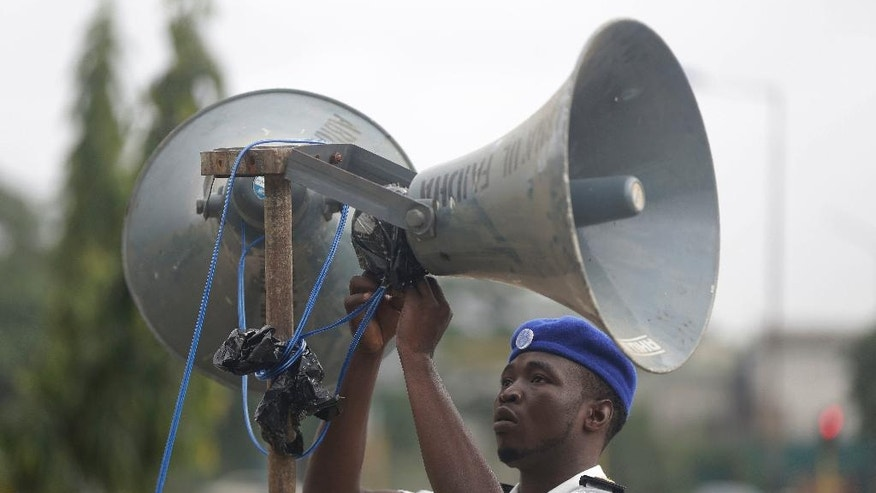 In this photo taken Wednesday July 6, 2016 a Muslim man attaches a megaphone in the street during Eid prayers in Lagos, Nigeria. Officials in Nigeria's biggest city are closing down dozens of churches, mosques and nightclubs in a bid to reduce noise in Lagos, the seaside commercial center where honking horns and thrumming generators compete with lusty hymn-singing and loudspeakers calling people to prayer. (AP Photo/Sunday Alamba)