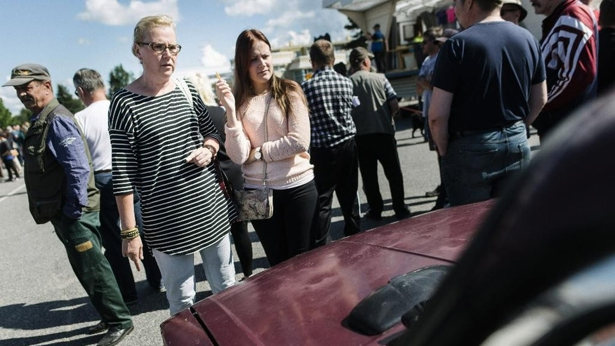 Kristiina Lappalainen and daughter Malla view one of the cars on auction during an auction as Asylum seekers' abandoned cars in Salla, northern Finland, on Friday July 15, 2016. Over 100 old cars, mostly Russian-made, driven across the northeastern Finnish border by asylum seekers and abandoned at the Salla border crossing point this past winter are auctioned in a two-day event in Salla. (Jouni Porsanger/Lehtikuva via AP)  FINLAND OUT - NO SALES