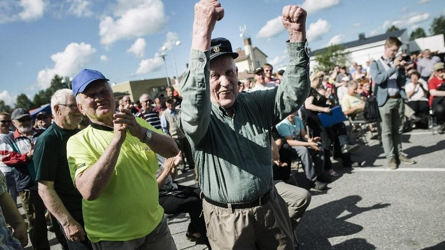 Huugo Jaakkonen from Salla, Finland, celebrates his 60 euro winning bid on the first car auctioned as Asylum seekers' abandoned cars are sold off in Salla, northern Finland, on Friday July 15, 2016. Over 100 old cars, mostly Russian-made, driven across the northeastern Finnish border by asylum seekers and abandoned at the Salla border crossing point this past winter are auctioned in a two-day event in Salla. (Jouni Porsanger/Lehtikuva via AP)  FINLAND OUT - NO SALES