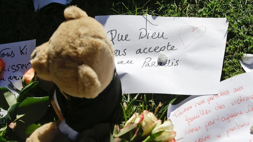 A teddy bear sits with flowers and paper tributes on the Promenade des Anglais near the scene of a truck attack in Nice, southern France, Saturday, July 16, 2016. Nice's seaside boulevard reopens to traffic Saturday following a dramatic truck attack which killed more than 80 people and wounded more than 200 others at a fireworks display. (AP Photo/Luca Bruno)