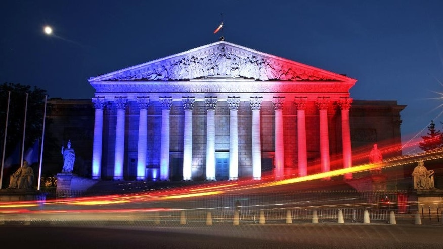 Cars pass by the National Assembly illuminated in the French national colors in honor of the victims of Thursday's attack in Nice, south of France, in Paris Friday, July 15, 2016. As new details emerged Friday about the Tunisian man who drove a truck through crowds celebrating Bastille Day in Nice, killing at least 80 people and wounding hundreds others, French leaders extended a state of emergency imposed after the Nov. 13 Paris attacks and vowed to deploy thousands of police reservists on the streets. (AP Photo/Thibault Camus)