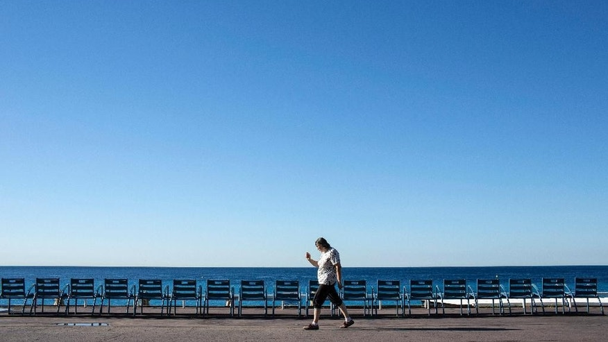 A woman walks on the Promenade des Anglais in Nice, southern France, Saturday, July 16, 2016. Nice's seaside boulevard reopens to traffic Saturday following a dramatic truck attack which killed more than 80 people and wounded more than 200 others at a fireworks display. (AP Photo/Laurent Cipriani)