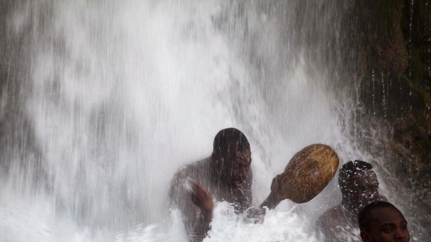 A voodoo pilgrim bathes as he prays in a waterfall believed to have purifying powers during the annual celebration in Saut d' Eau, Haiti, Saturday, July 16, 2016. After bathing, voodoo pilgrims throw away the dresses they wore to the site, and don new clothes for good luck. ( AP Photo/Dieu Nalio Chery)