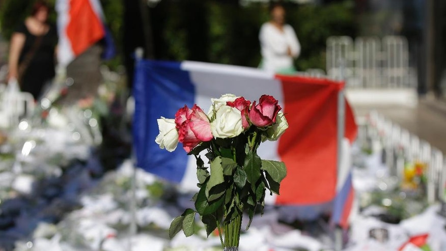 Floral and papers tributes are laid with a French flag near the scene of a truck attack in Nice, southern France, Saturday, July 16, 2016. Nice's seaside boulevard reopens to traffic Saturday following a dramatic truck attack which killed more than 80 people and wounded more than 200 others at a fireworks display. (AP Photo/Luca Bruno)