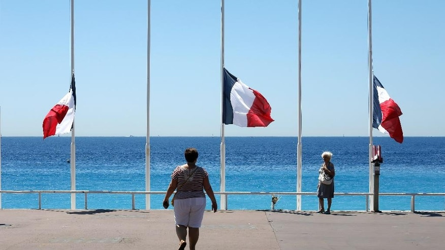People stroll on the Promenade des Anglais with the French flag at half mast,  near the scene of a truck attack in Nice, southern France, Saturday, July 16, 2016. The man responsible for turning a night of celebration into one of carnage in the seaside city of Nice was a petty criminal who hadn't been on the radar of French intelligence services before the attack. (AP Photo/Laurent Cipriani)