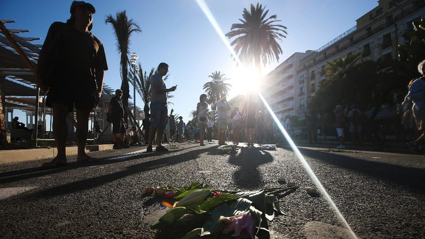 "People lay flowers at the site of a deadly truck attack on the famed Promenade des Anglais in Nice, southern France, Saturday, July 16, 2016. French Interior Minister Bernard Cazeneuve says that the truck driver who killed 84 people when he careened into a crowd at a fireworks show was ""radicalized very quickly."" (AP Photo/Luca Bruno)"