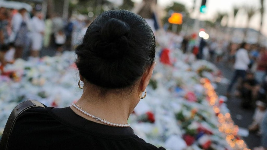 "A woman pays tribute to the victims of a deadly truck attack at the site of the attack on the famed Boulevard des Anglais in Nice southern France, Saturday, July 16, 2016. French Interior Minister Bernard Cazeneuve says that the truck driver who killed 84 people when he careened into a crowd at a fireworks show was ""radicalized very quickly."" (AP Photo/Laurent Cipriani)"