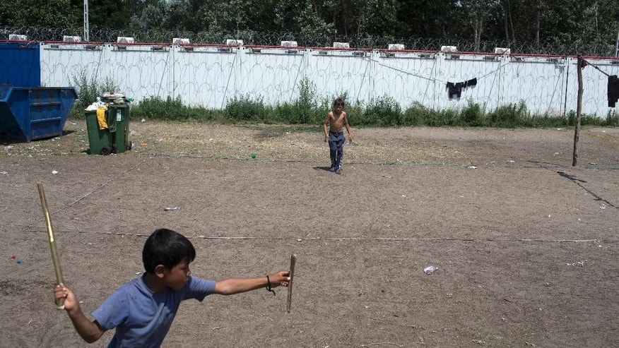 Children play a game at a migrant camp at Serbia's border with Hungary, in Horgos, Serbia, Wednesday, July 13, 2016. Hungarian police and soldiers have beaten some migrants severely before sending them back across the border to Serbia, Human Rights Watch said in a report released Wednesday. (AP Photo/Marko Drobnjakovic)