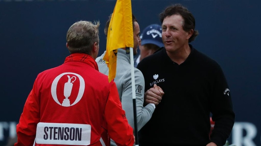 Phil Mickelson of the United States, right, shakes hands with Henrik Stenson of Sweden,on the 18th green after they completed their third round of the British Open Golf Championships at the Royal Troon Golf Club in Troon, Scotland, Saturday, July 16, 2016. (AP Photo/Ben Curtis)