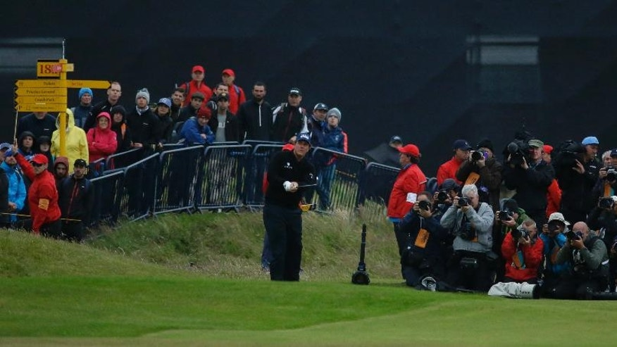 Phil Mickelson of the United States hits a shot from the 18th fairway, with the media bunched to his left to record his shot, during the third round of the British Open Golf Championship at the Royal Troon Golf Club in Troon, Scotland, Saturday, July 16, 2016. (AP Photo/Matt Dunham)