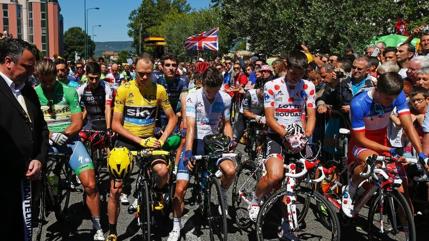 The pack with Peter Sagan of Slovakia, wearing the best sprinter's green jersey, Britain's Chris Froome, wearing the overall leader's yellow jersey, Britain's Adam Yates , wearing the best young rider's white jersey, and Belgium's Thomas de Gendt, wearing the best climber's dotted jersey observe a minute of silence to commemorate the victims of the Nice truck attack, before the start of the fourteenth stage of the Tour de France cycling race over 208.5 kilometers (129.2 miles) with start in Montelimar and finish in Villars-les-Dombes, France, Saturday, July 16, 2016. A Frenchman of Tunisian descent drove a truck through crowds celebrating Bastille Day along Nice's beachfront, killing at least 84 people, many of them children. (AP Photo/Peter Dejong)