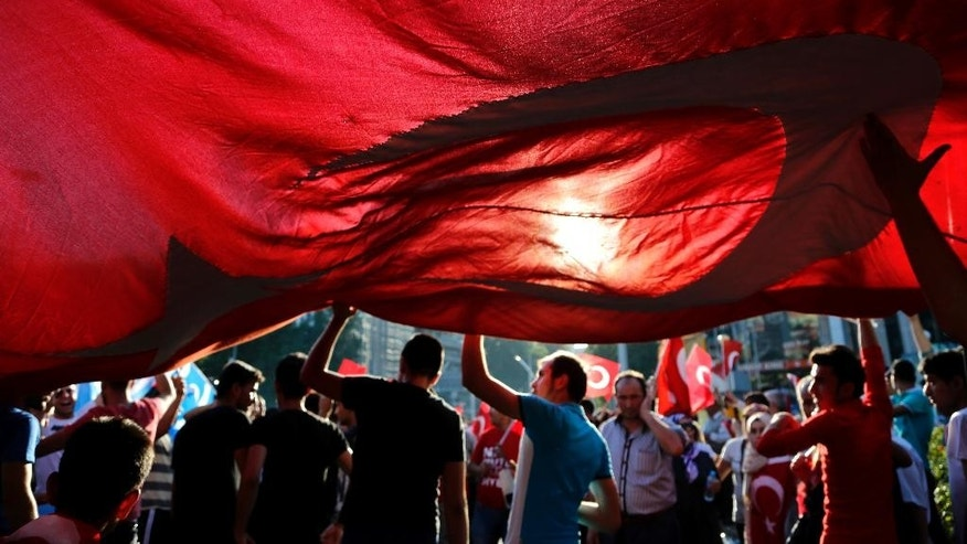 Turkish citizens wave a huge national flag as they protest against the military coup outside Turkey's parliament near the Turkish military headquarters in Ankara, Turkey, Saturday, July 16, 2016. Forces loyal to Turkey's President Recep Tayyip Erdogan quashed a coup attempt in a night of explosions, air battles and gunfire that left dozens dead Saturday. (AP Photo/Hussein Malla)