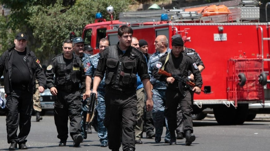 Armenian police and special force secure the area around a police station in Yerevan, Armenia, Sunday, July 17, 2016. Armenia security forces say a group of armed men has attacked a central police station in the Armenian capital, killing one officer, wounding two and taking others hostage. (Aram Kirakosyan/PAN Photo via AP)