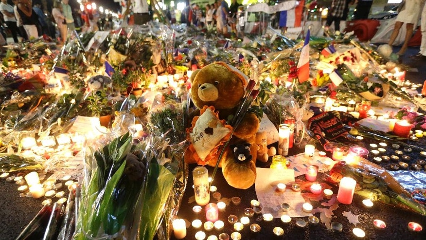 A teddy bear is laid with flowers and candles to honor the victims of an attack, on the Promenade des Anglais, near the area where a truck mowed through revelers in Nice, southern France, Saturday, July 16, 2016. A large truck mowed through revelers gathered for Bastille Day fireworks in Nice, killing scores of people and sending people fleeing into the sea as it bore down for more than a mile along the Riviera city's famed waterfront promenade. (AP Photo/Claude Paris)