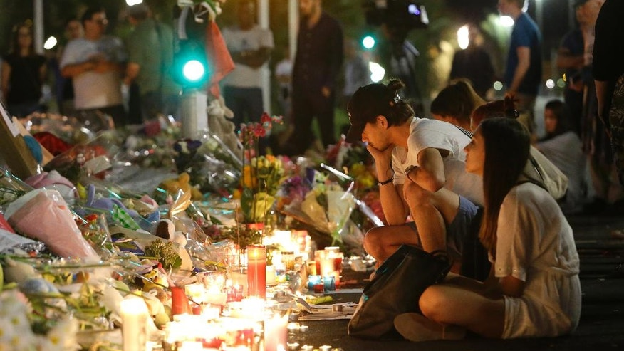 People gather at a makeshift memorial to honor the victims of an attack, near the area where a truck mowed through revelers in Nice, southern France, Saturday, July 16, 2016. A large truck mowed through revelers gathered for Bastille Day fireworks in Nice, killing scores of people and sending people fleeing into the sea as it bore down for more than a mile along the Riviera city's famed waterfront promenade. (AP Photo/Claude Paris)