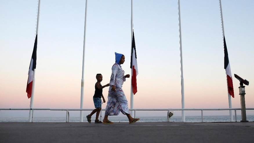 """A woman and her child pass by French flags at half mast near the site of a deadly attack on the famed Boulevard des Anglais in Nice southern France, Saturday, July 16, 2016. French Interior Minister Bernard Cazeneuve says that the truck driver who killed 84 people when he careened into a crowd at a fireworks show was """"radicalized very quickly."""" (AP Photo/Laurent Cipriani)"""