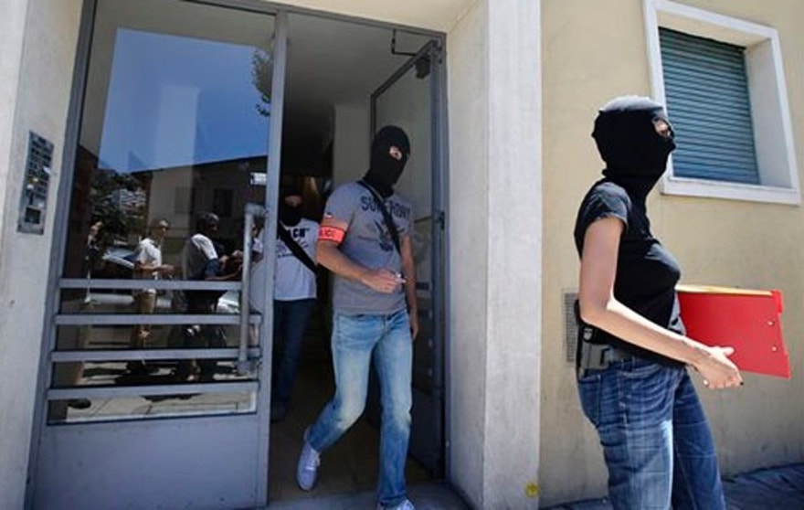 French hooded police officers leave the building where lived Mohamed Lahouaiej Bouhlel, in Nice, southern France, Saturday, July 16, 2016. The man responsible for turning a night of celebration into one of carnage in the seaside city of Nice was a petty criminal who hadn't been on the radar of French intelligence services before the attack.  (AP Photo/Luca Bruno)
