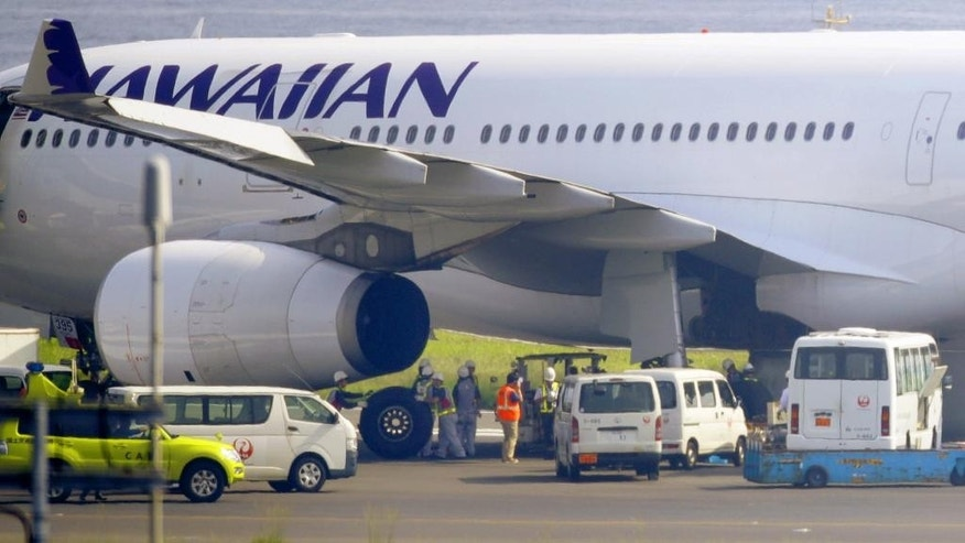 A Hawaiian Airlines jet is seen on tarmac after making an emergency landing at Haneda airport in Tokyo, Monday, July 18, 2016.  A runway is closed at the Tokyo's main airport after the jet punctured tires while making an emergency landing. Japanese media report that eight tires blew out when the Airbus A330 returned to Haneda Airport early Monday morning after a display indicated a problem in the hydraulic system. (Hiroki Yamauchi/Kyodo News via AP) JAPAN OUT, CREDIT MANDATORY