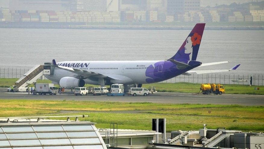 A Hawaiian Airlines jet is seen on tarmac after making an emergency landing at Haneda airport in Tokyo, Monday, July 18, 2016.  A runway is closed at the Tokyo's main airport after the jet punctured tires while making an emergency landing. Japanese media report that eight tires blew out when the Airbus A330 returned to Haneda Airport early Monday morning after a display indicated a problem in the hydraulic system. (Hiroki Yamauchi/Kyodo News via AP)