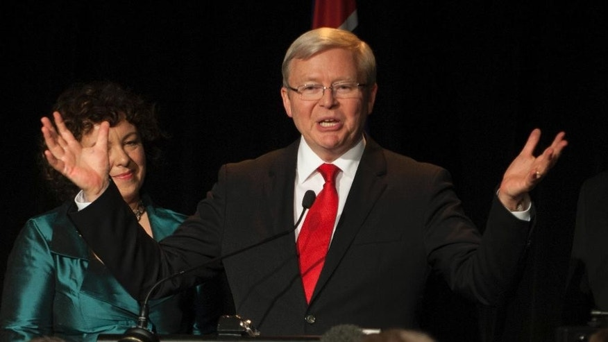 FILE - In this Sept. 7, 2013 file photo, then Australian Prime Minister Kevin Rudd, right, addresses his party members during an Australian Labor Party election night function in Brisbane. Former Australian Prime Minister Kevin Rudd is making a late bid for the top United Nations job, after months of cross-crossing the world in low-key lobbying for government support. Rudd had requested that the Australian government take the crucial step of formally nominating him to succeed U.N. Secretary-General Ban Ki-moon, whose second five-year term ends Dec. 31. At left is his wife Therese Rein.  (AP Photo/John Pryke, File)