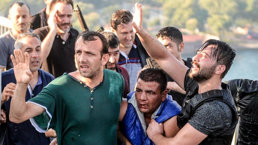 People apprehend a Turkish soldier, center in blue, that participated in the attempted coup, on Istanbul's Bosporus Bridge, Saturday, July 16, 2016. Turkish President Recep Tayyip Erdogan told the nation Saturday that his government was working to crush a coup attempt after a night of explosions, air battles and gunfire across the capital that left dozens dead and scores wounded. Government officials said the coup appeared to have failed as Turks took to the streets overnight to confront troops attempting to take over the country. (AP Photo/Selcuk Samiloglu)