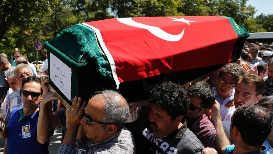 Mourners carry the coffin of Turkish geologist Cuma Dag, 39, during his funeral procession in Ankara, Turkey, Sunday July 17, 2016, who was killed by helicopter gunfire last Friday while protesting against the attempted coup against Turkey's government. Rather than toppling Turkey's strongman president, a failed military coup that left more than 250 dead appears to have bolstered Recep Tayyip Erdogan's immediate grip on power and boosted his popularity. (AP Photo/Hussein Malla)