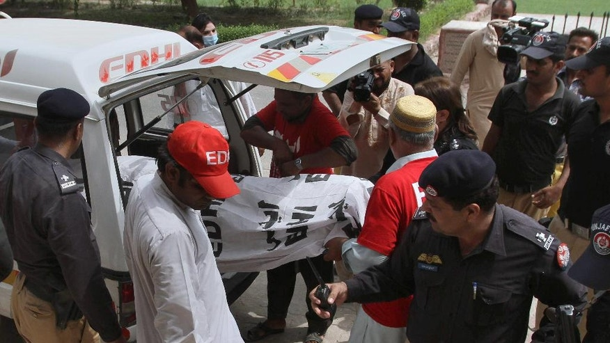 Pakistani police officers stand beside volunteers unloading the dead body of fashion model Qandeel Baloch upon arrival at a local hospital in Multan, Pakistan, July 16, 2016. Baloch, who recently stirred controversy by posting pictures of herself with a Muslim cleric on social media, was strangled to death by her brother, police said Saturday, July 16, 2016. (AP Photo/Asim Tanveer)