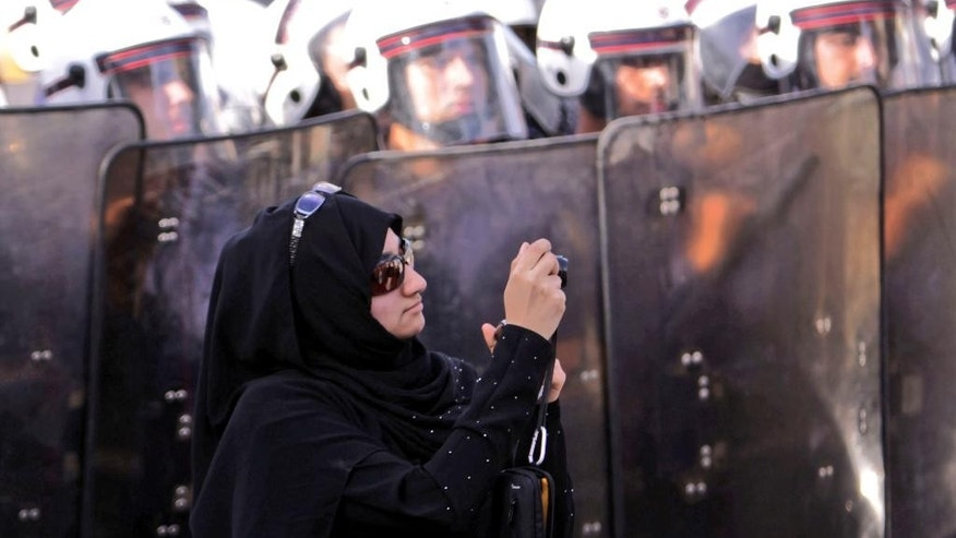 FILE- In this Jan. 18, 2012 file photo, an anti-government protester stands in front of riot police while photographing other demonstrators in Manama, Bahrain. Local media in Bahrain are reporting that a court has ordered the country's main Shiite opposition group to be dissolved. The order against Al-Wefaq follows an intensified crackdown on dissent in the Sunni-ruled island kingdom, which is home to the U.S. Navy's 5th Fleet. (AP Photo/Hasan Jamali, File)