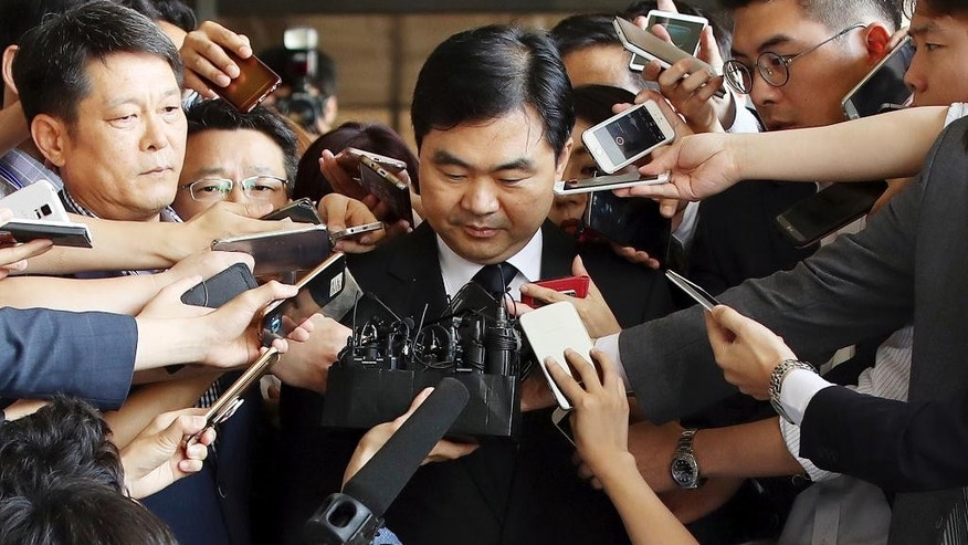 In this Thursday, July 14, 2016 photo, a senior South Korean prosecutor Jin Kyung-joon, center, is surrounded by media upon his arrival for questioning at the Seoul Central District Prosecutors' Office in Seoul, South Korea.  Senior prosecutor Jin has been arrested for allegedly pocketing millions of dollars following shady stock transaction deals with a leading online game maker. (Park Dong-ju/Yonhap via AP)
