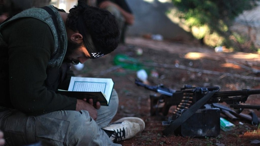 FLE -- In this Nov. 15, 2012 file photo, a Syrian rebel reads Quran during clashes with government forces in Aleppo, Syria. Syrian opposition activists said Sunday, July 17, 2016 that government forces and their allies have closed the only road leading into and out of rebel-held parts of the northern city of Aleppo, besieging hundreds of thousands of people. The Britain-based Syrian Observatory for Human Rights says government forces and members of Lebanon's Hezbollah group reached the Castello road Sunday, closing it and raising fears of a humanitarian crisis. (AP Photo/ Khalil Hamra, File)