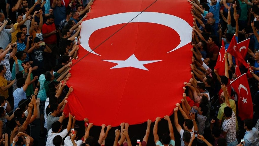 People gather at a pro-government rally in central Istanbul's Taksim square, Saturday, July 16, 2016. Forces loyal to Turkish President Recep Tayyip Erdogan quashed a coup attempt in a night of explosions, air battles and gunfire that left some hundreds of people dead and scores of others wounded Saturday. (AP Photo/Emrah Gurel)