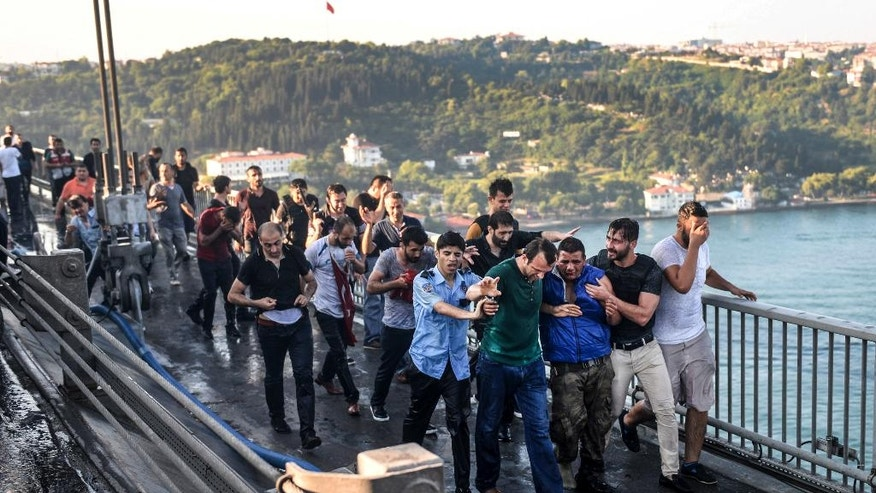 People apprehend a Turkish soldier, third right in blue, that participated in the attempted coup, on Istanbul's Bosporus Bridge, Saturday, July 16, 2016. Turkish President Recep Tayyip Erdogan told the nation Saturday that his government was working to crush a coup attempt after a night of explosions, air battles and gunfire across the capital that left dozens dead and scores wounded. Government officials said the coup appeared to have failed as Turks took to the streets overnight to confront troops attempting to take over the country. (AP Photo/Selcuk Samiloglu)