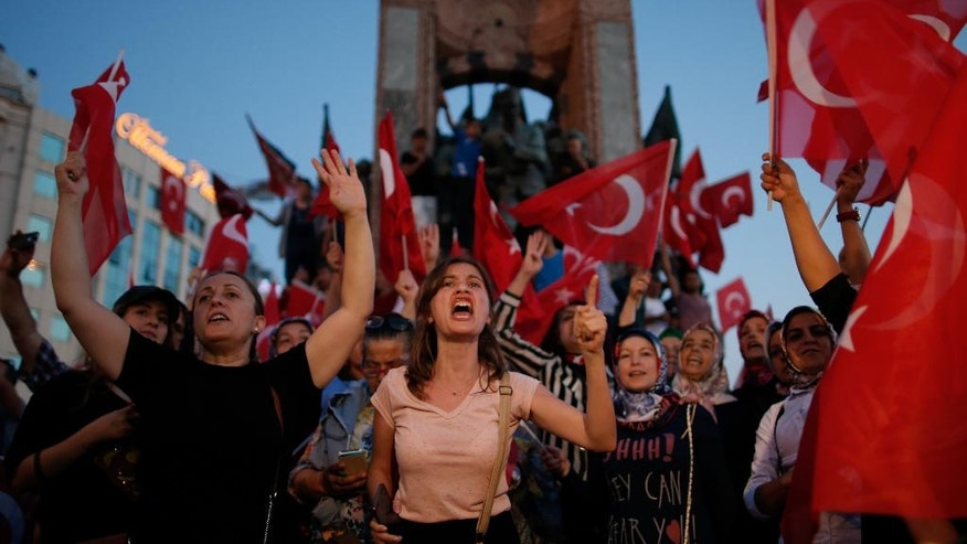 People chant slogans as they gather at a pro-government rally in central Istanbul's Taksim square, Saturday, July 16, 2016. Forces loyal to Turkish President Recep Tayyip Erdogan quashed a coup attempt in a night of explosions, air battles and gunfire that left some hundreds of people dead and scores of others wounded Saturday.  (AP Photo/Emrah Gurel)