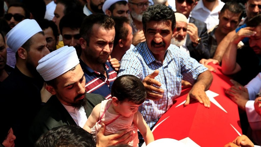 Mourners bring a child next to the Turkish flag-draped coffin of their loved one, during a funeral for people killed Friday while protesting the attempted coup against Turkey's government, in Istanbul, Sunday, July 17, 2016. Rather than toppling Turkey's strongman president, a failed military coup appears to have bolstered Recep Tayyip Erdogan's immediate grip on power and boosted his popularity. (AP Photo/Lefteris Pitarakis)